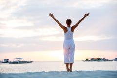 妇女做着瑜伽锻炼在博拉凯海岛上的日落, 免版税图库摄影