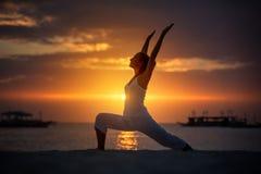 妇女做着瑜伽锻炼在博拉凯海岛上的日落, 免版税库存照片