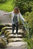 妇女做试探性小河横穿 免版税图库摄影