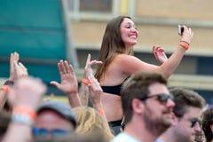 妇女做selfie从观众上在生波探侧器节日 免版税库存照片