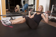 妇女健身房坐直与酒吧 库存图片
