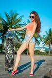 妇女全长画象戴摆在与longboard的眼镜的在棕榈附近在热带国家 免版税库存图片