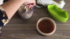 妇女关上搅拌器碗的盒盖和研磨花生和种子做的halva 在容器旁边是增加的蜂蜜 股票视频