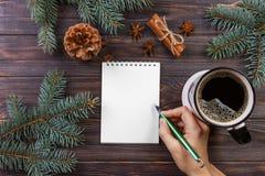 妇女写愿望或做在笔记本,咖啡杯,圣诞节的名单 圣诞树分支,杉木锥体,红色莓果,在大理石t 免版税库存照片