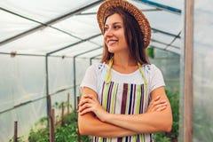 妇女农夫身分自温室 愉快的工作者增长的菜和感到骄傲为她的工作在温室里 免版税库存图片