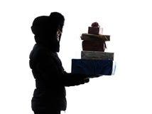 妇女冬天外套运载的圣诞节礼物剪影 免版税库存图片