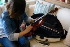 妇女准备从小提琴盒的小提琴在沙发 免版税库存照片