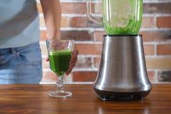 妇女准备喝绿色圆滑的人 库存图片