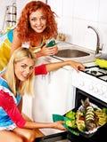 妇女准备在烤箱的鱼。 免版税库存图片
