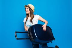 妇女准备好在蓝色背景隔绝的夏天旅行 跑与在蓝色背景的行李的俏丽的妇女 免版税库存照片