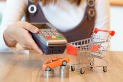 妇女准备好对支付有红色购物车的c一辆新的汽车 免版税图库摄影