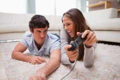 妇女击败了她的男朋友在一个电子游戏 免版税库存照片