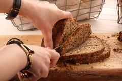 妇女切了在一个木板的整个五谷面包 免版税库存照片
