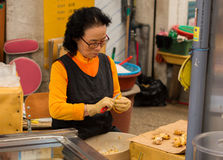 妇女切口姜在Dongmun市场上 免版税库存图片