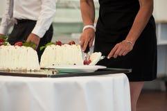 妇女切口婚宴喜饼在招待室 免版税库存照片