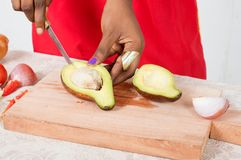 妇女切口鲕梨的手 库存图片