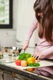 妇女切开一个黄瓜和菜与刀子 在家烹调在厨房里的少妇 健康的食物 饮食 库存图片