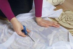 妇女切开与剪刀的织品在窗口的缝合的帷幕的 织品在地板上说谎 在视图之上 免版税库存图片