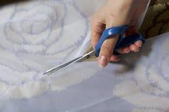 妇女切开与剪刀的织品在窗口的缝合的帷幕的 织品在地板上说谎 在视图之上 免版税库存照片
