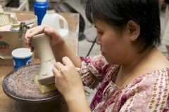 妇女切开传统纹身花刺动机装饰在白陶土,古晋,马来西亚 库存照片