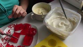 妇女切草莓果冻 它在有一个红色样式的一个白色茶碟说谎 附近做的点心硅树脂模子 影视素材