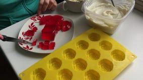 妇女切草莓果冻 它在有一个红色样式的一个白色茶碟说谎 附近做的点心硅树脂模子 股票录像
