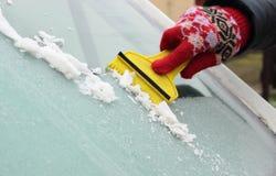 妇女刮的冰的手从汽车挡风玻璃的 免版税库存照片