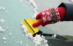 妇女刮的冰的手从汽车挡风玻璃的 免版税图库摄影