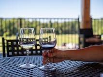 妇女到达为几乎空的杯的` s胳膊在一张室外餐桌上的红色和白葡萄酒 库存照片