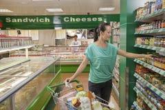 妇女到达为在架子的瓶子的在超级市场,北京 库存照片