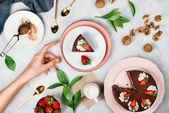 妇女到达为素食主义者核桃、草莓、可可粉和其他点心ing围拢的巧克力蛋糕片断的` s手  库存图片