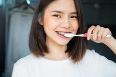 妇女刷佩带括号的牙,在洗手间 必须维护好口头健康 图库摄影