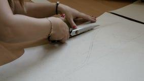 妇女削减缝合的礼服的样式 工作在她的陈列室的设计师做缝合的样式在纺织品 影视素材