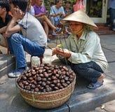 妇女削皮栗子在河内越南 库存照片