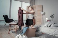 妇女前夫包装衣裳到箱子和哭泣里 免版税库存照片