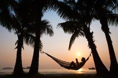 在吊床的日落在海滩 免版税库存照片