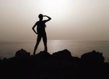 妇女剪影在山上面的  免版税库存图片