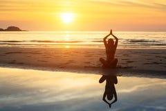 妇女剪影坐海滩在美好的日落期间 免版税图库摄影
