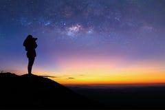 妇女剪影拍银河照片在山顶部 免版税库存图片