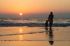妇女剪影有孩子的海滩的 免版税图库摄影