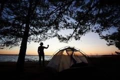 妇女剪影海岸的在有照片照相机的旅游帐篷附近,拍照片 免版税库存图片