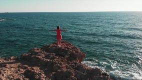 妇女剪影用分开手在岩石峭壁的空气身分反对太阳和太阳路 红色礼服拍动的女孩在风与 股票视频