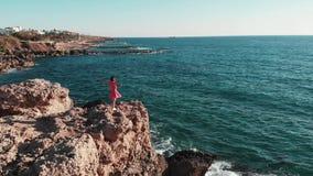 妇女剪影用分开手在岩石峭壁的空气身分反对太阳和太阳路 红色礼服拍动的女孩在风与 股票录像
