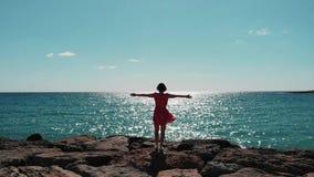 妇女剪影红色礼服的有分开胳膊的在多岩石的海滩码头的空气身分反对与拍动她的礼服的风的太阳 美国兵 股票录像