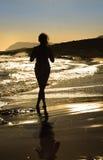 妇女剪影走在一个空的海滩的-在风的头发在 免版税库存图片