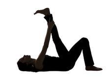 妇女剪影,舒展在瑜伽的斜倚的腿 免版税库存图片