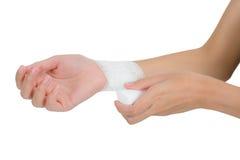 妇女包扎的和急救她美丽的健康腕子在痛苦区域 免版税库存照片