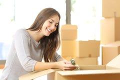 妇女包装或打开移动的家 免版税库存照片