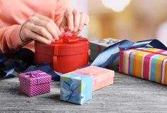 妇女包装礼物的手 图库摄影