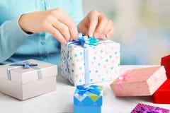 妇女包装礼物的手 库存照片